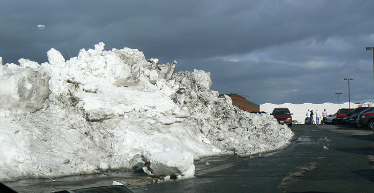 photo of giant pile of snow in a parking lot