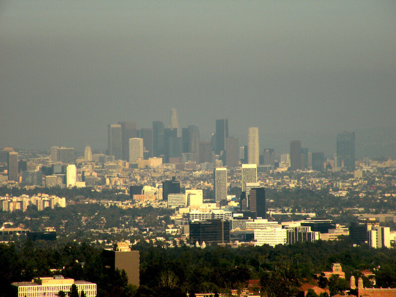 a photograph of a blue sky with smog in front of the skyscrapers of the Los Angeles skyline
