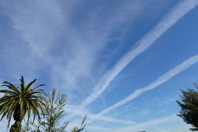 photo of white streaks of contrails in the sky