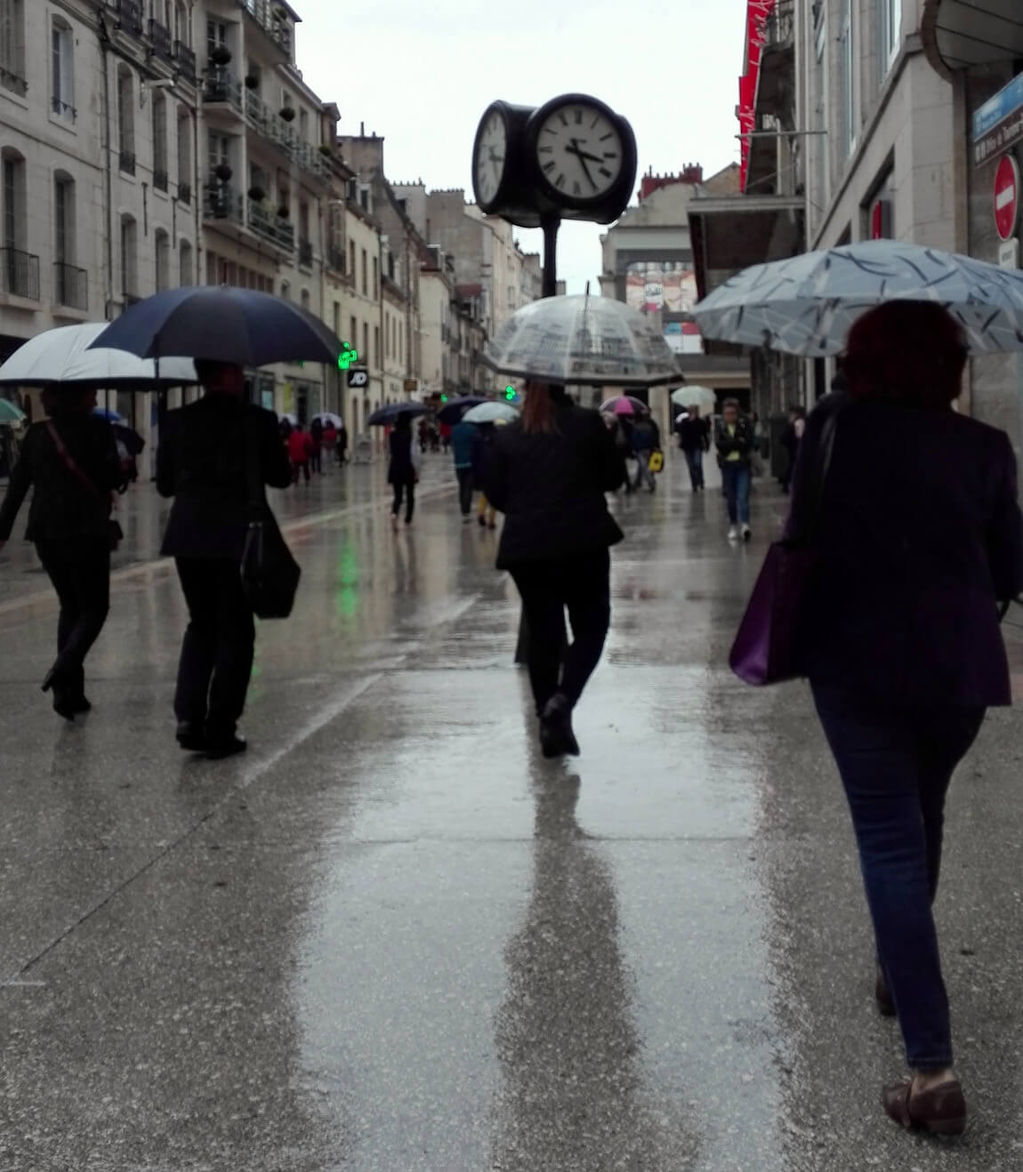 a photograph of people using umbrellas in the rain