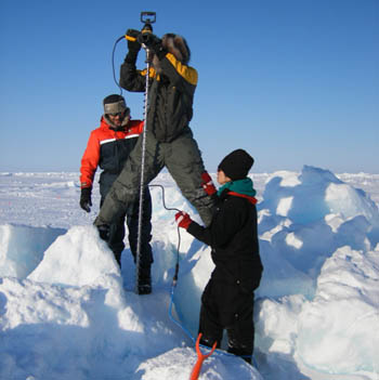 Photograph of Dr Clemente-Colón and his team drilling ice.