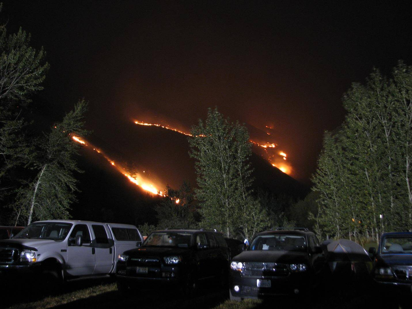 Photo of an incident command post near burning wild fire.