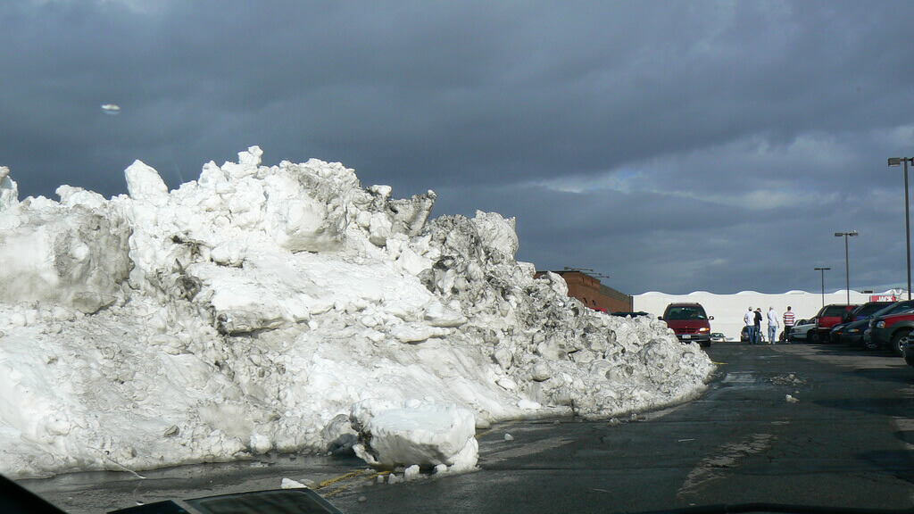 photograph of a parking lot with a massive pile of snow from plowing.