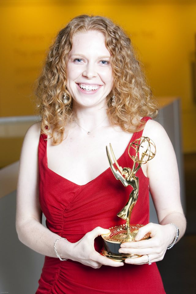 Photo of Carrie Rose holding an Emmy award.