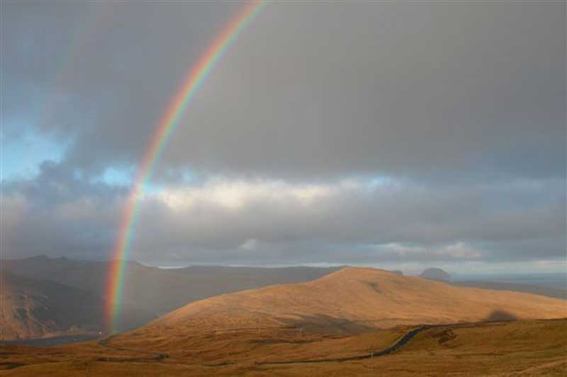 Photo of rainbow arc over brown hills, with road.
