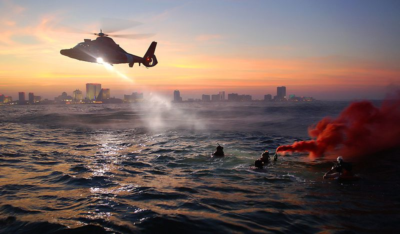 photograph of a USCG training excercise with a helicopter and rescue swimmers.