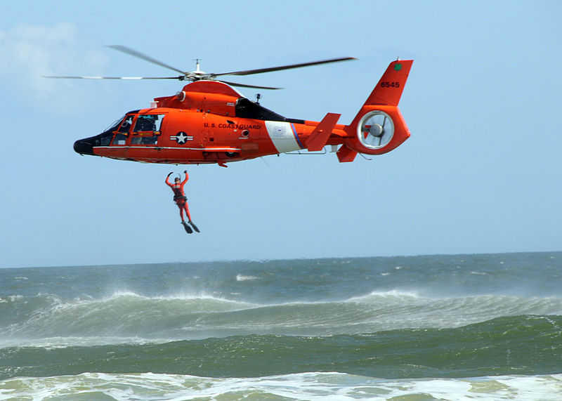 photo of a Coast Guardsman jumping into water from a helicopter.