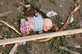 Photo of doll lying on ground surrounding by scraps of debris.