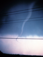Photo of a funnel cloud hanging in the sky, not touching the ground.